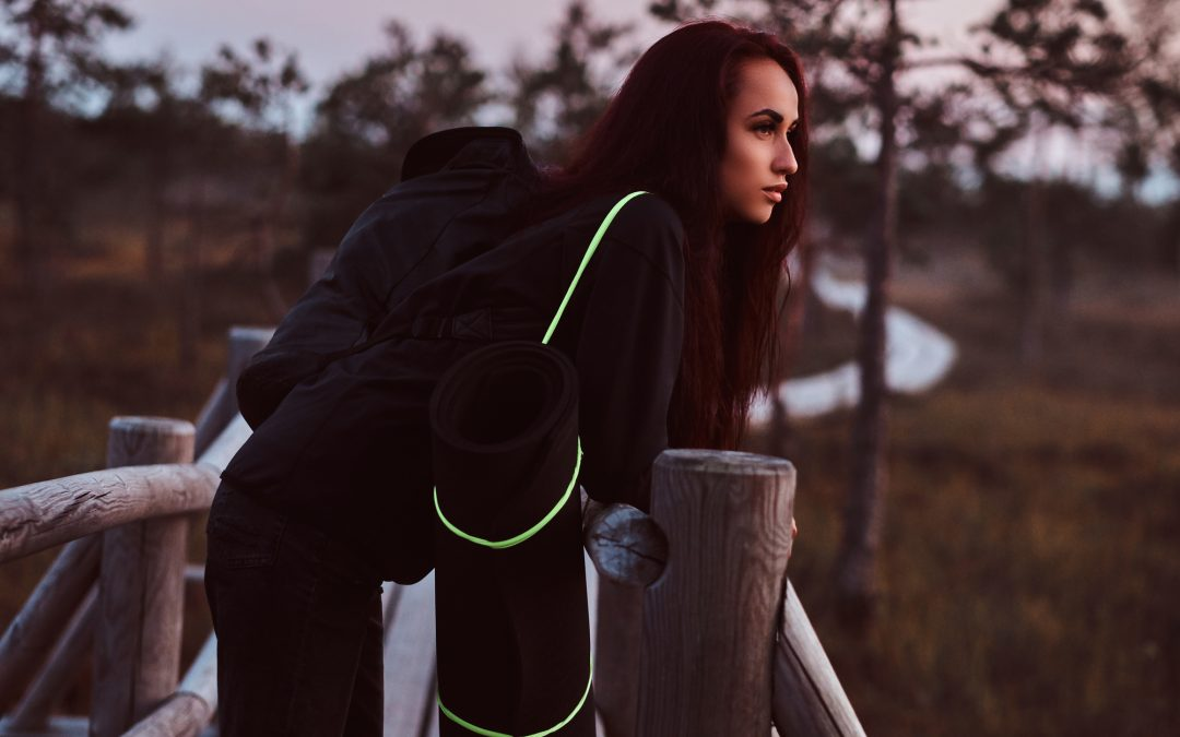 Woman in a black hoodie and jeans leaning on a wooden fence in a beautiful autumn meadow at sunset.